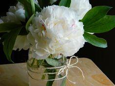 sweet and simple center piece. seasonal flowers, mason jar and jute.