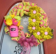 "Springtime wreath, mason jar, various colored flowers, added a personal touch with the monogramed ""L"", and added a pink bow as a finishing touch."
