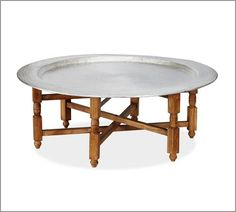 Patterned after a traditional Moroccan tea table, this piece provides an intimate gathering place for friends and family. The hand-hammered aluminum top lifts off easily, and the acacia wood frame and spindle-turned legs fold for quick storage.