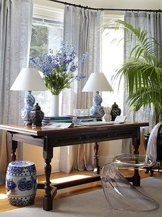 Wood desk with lucite chair - blue and white ceramics - desk arrangement in front of window