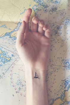 "Sailboat tattoo with the word ""wanderlust"" as the waves"
