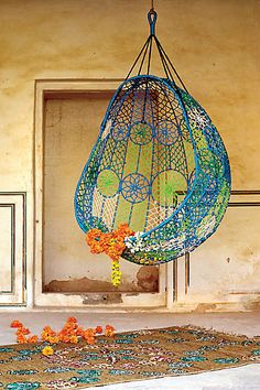 """Knotted Melati Hanging Chair in blue motif - """"Sling this pod of [blue and green] hued macrame from porch rafters or tree branches or even living room beams.""""  