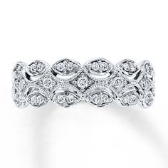 Scallops of 10K white gold and milgrain detailing give this romantic anniversary band for her a distinctly vintage feel. Round diamonds twinkle along the ring, with a total diamond weight of 1/4 carat. Diamond Total Carat Weight may range from .23 - .28 carats.