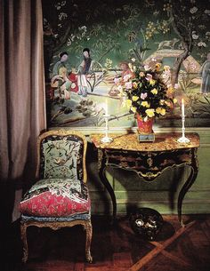 The table is Louis XV in black and gold vernis martin with figures in the Chinese taste. On top are Battersea white and green enamel candlesticks and an 18th-century tole vase filled with roses from the garden.