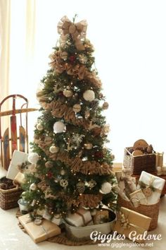 Use a DIY garland, flashes of red, and wood slice ornament to pull off an effortlessly rustic look. See more at Giggles Galore. Christmas Tree Game, Best Christmas Tree Decorations, Country Christmas Trees, Creative Christmas Trees, Burlap Christmas Tree, Traditional Christmas Tree, Woodland Christmas, Beautiful Christmas Trees, Noel Christmas