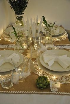 Pretty table setting. Paper doilies over burlap, white string lights, Christmas trees made from old sheet music, and a silver ice bucket to hold white taper candles. Shabby chic.