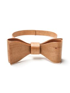 """Wooden bow tie The Wooden Bow Ring, a part of our Tea Party collection, is handmade for us by the Icelandic cabinet maker Muggi. He developed an extraordinary technique to bend strips of wood to form the elegant bow and then added another technique of his to tan the ash wood by """"burning it"""" (so says the man himself!), adding the beautiful tone to it."""