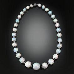 Thirty-one stunning opal beads totaling an extraordinary 540 carats comprise this mesmerizing necklace. The graduated gems are an impressive size, with each exhibiting a high level of translucence and a rainbow of colors. To find 31 all-natural, matching beads of this giant size and exceptional quality is extraordinary beyond compare. Each resplendent orb is separated by elegant white gold rondells set with 5.23 carats of shimmering diamonds and secured with a pavé diamond ball…