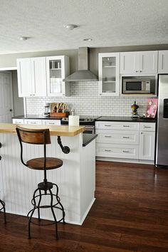 This goes into my top favorite kitchens! White with black countertops and vintage industrial bar stools.