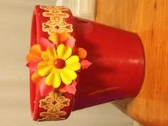 Decorated flower pot. Took an ordinary colored pot and used scrapbook embellishments to give it character! Endless possibilities!