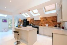 beautiful kitchen with brick backsplash #veluxextension