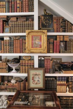 Classic books fill shelves under a staircase; gilded frames, old prints, shadow box, antique objects.
