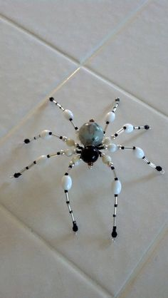 This spooky beaded spider is perfect for your Halloween decorations. It is made with black, white, silver, and a sesame jasper bead. It is about four