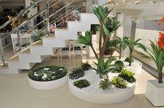 Neste projeto, dos arquitetos Claudia Ruzzarin Veronese e Gildo Felipe Muner, o objetivo foi criar floreiras em forma de círculo. Confeccionadas em MDF, receberam pintura em laca branca, com rodízios para facilitar a limpeza e manutenção e para preencher o espaço embaixo da escada, fazendo um grande jardim de plantinhas de várias alturas.