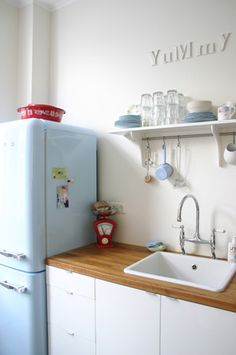 white cabinets / butcher block counter / vintage fridge