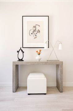Light walls, light wood floors, concrete console, white ceramic vase, silver and white lamp, and a white leather stool