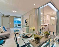 A divisão entre o quarto e a sala de estar é feita por lâminas de vidro. No quarto, prateleiras iluminadas de vidro e lustre do mesmo material. A mesa de jantar e cadeiras também são de vidro. Projeto da arquiteta Fernanda de Lima.