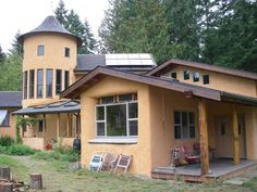 A gorgeous straw bale home finished.  I love the deep window wells and the turret.
