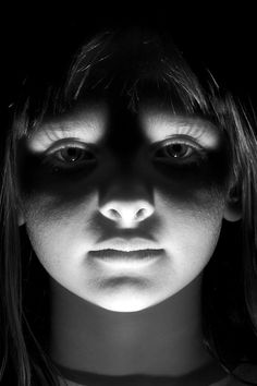 This girl has up light on her face, presumably from a flashlight or other artificial source of light. Since it is unusual for natural light to be shining up, this picture takes on a creepy feeling. I think it is interesting that this girl becomes scary and almost threatening just because of the way the light is hitting her. If the light were hitting her face in a natural way, I think my reaction to the picture would be entirely different because she isn't making a threatening face at all.