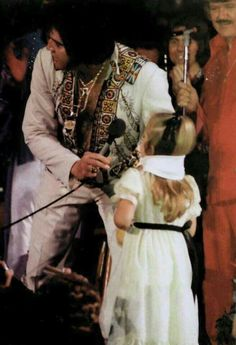 Elvis always loved his fans but this was so cute. Oh to be a little kid, to get a scarf. a kiss and be on stage with him what a night. Something this little girl will never forget