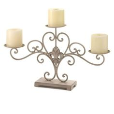 "by Gallery of Light Decorate your home with a little French flair and a whole lot of candlelight with this beautiful stand. The scrolling metal curls are embellished with a stylized fleur de lis symbol in the center and hold three candle platforms that are ready for the pillar candles of your choice.  The vintage patina makes this pretty candle display look like a lifelong treasure. Works perfectly on a mantel or sofa table, and also makes a great centerpiece for your dining room. 19.8"" x 4""…"