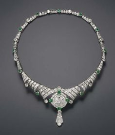 AN ART DECO EMERALD & DIAMOND NECKLACE   The tapering flexible band, composed of a series of pierced old European or baguette-cut diamond links, alternately-spaced by diamond & emerald collets, the front enhanced by an old European & baguette-cut diamond circular plaque, accented by diamond & cabochon emerald collets, suspending a pendant of similar design, mounted in platinum, ca 1930, 14¾ ins.