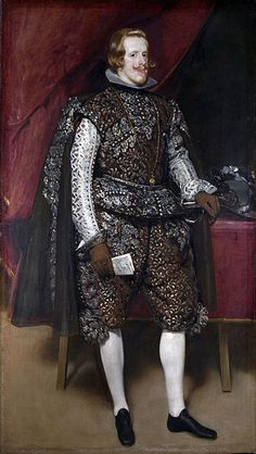 Philip IV of Spain wears breeches and doublet of brown and silver and a dark cloak all trimmed with silver lace. His sleeves are white and he wears white stockings, plain black shoes, and brown leather gloves, 1631–32. By Diego Valazquez.