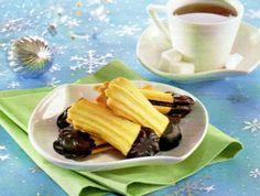 Změklé máslo utřeme s moučkovým i vanilkovým cukrem a žloutky do pěny. Vmícháme do ní jemně nastrouhanou pomerančovou kůru i šťávu a mouku. Hotové těsto dáme do cukrářského sáčku s řezanou trubičkou, kterým nastříkáme podlouhlé banánky na plech s pečícím papírem (můžeme tvarovat i pomocí strojku). Pečeme asi 12 minut na 180°C. Po upečení necháme vychladnout. Náplň: 100g másla utřeme se 100g rozpuštěné čokolády na vaření na hladký krém a slepíme vždy 2 sušenky k sobě. Konce banánků pak…