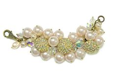 Crystal button bracelet, an uber-glamorous statement piece with aurora borealis crystal studded vintage buttons, vintage faux pearls, and vintage faceted crystal beads. Bling it on tastefully with this one of a kind creation! This piece looks so sumptuous on! It would be stunning on a bride or honored member of the wedding party. All the elements are securely wirewrapped to the brass chain. The chain is 7 inches (18 cm) in length. It closes with a pretty floral pattern brass lobster clasp.