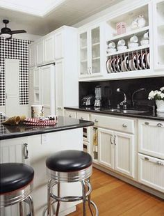 Black-granite countertops continue the diner theme while offering a durable work surface on both sides of this galley kitchen. Metal tiles on the backsplash enhance the retro feel. Specialized storage features such as the vertical-slat plate holder and a pullout pantry help the small space function in a big way. Total cost (excluding labor): $29,305/