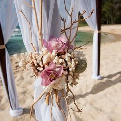 An Intimate Beachfront Destination Wedding in Kahuku, Hawaii = Seaside-inspired arrangements of coral, driftwood and orchids adorned the couple's wedding arch.
