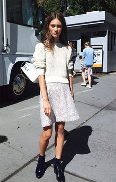 White sweater. Textured white skirt. Black boots.