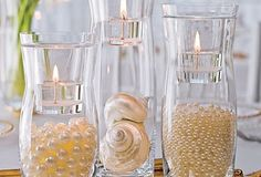 Another solution which doesn't need flowers  Fill the candle holders with fake pearls or other gems and add a candle.