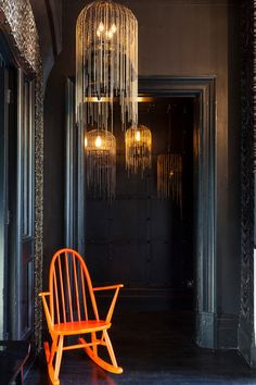 In the hallway leading to the master bedroom and Honey's room, Ellis and Hendrie added another set of hanging birdcages, which float ethereally against the black backdrop. The fluorescent orange chair is another antique the couple picked up and painted.