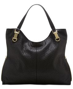 Perfectly proportioned for the gal on the go, this handbag from Vince Camuto features sturdy leather construction bedecked with gold-tone hardware accents. With a super spacious interior, it's ideal f