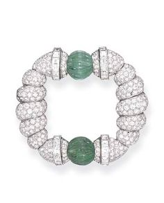 AN ART DECO DIAMOND AND EMERALD BROOCH, BY TIFFANY  CO.  Designed as a fluted pavé-set diamond openwork plaque of circular outline, enhanced by two carved emerald beads, further accented by baguette-cut diamonds, mounted in platinum, circa 1925 Signed Tiffany  Co., no. 7511
