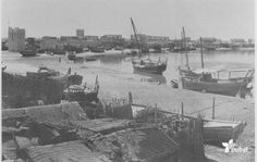 Old Dubai Creek in 1951. Dubai creek was surrounded with both Huts and Sand Stone Houses. Date palm had been used to built these Huts. Dhows were the only means to cross the Creek at this time.