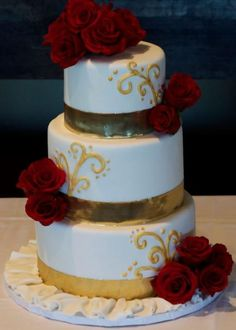 Tri-tier round white wedding cake with fresh red roses and gold bands.JPG