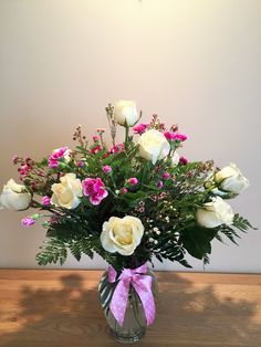 Purple Haze includes a dozen white roses sprinkled with purple wax flower and carnations.  flower arrangement