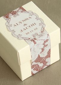 """Enchant your guests with this lovely white favor box. Personalized adhesive strip features a delicate lace pattern and intricately cut border in Rosewood. Add your first names and wedding date to commemorate your big day! Features and Facts:  Kit includes: 2"""" x 2"""" x 2"""" white box and personalized adhesive strip.  Easy assembly required.  Personalization Parameters:  Line 1: Bride's First Name (26 characters).  Line 2: & (ampersand).  Line 3: Groom's First Name (26 characters).  Line 4…"""