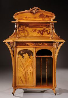 """Emile Gallé music cabinet in walnut with rosewood veneer, marquetry background depicting a landscape with exotic butterflies, carved floral cornice work. The curved base and ribbed ends with bronze feet. Signed """"Gallé"""". 1900."""