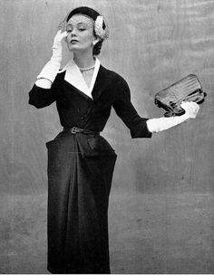 1951 Model in elegant afternoon dress of black alpaca with assymetrical collar of white piqué, by Jeanne Lafaurie, hat by Rose Valois