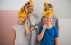 Familia delante de una pared con máscaras y coronas hechas con hojas de árbol.