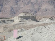 ziggurat stands amidst ashen ruins in Gomorrah, with darker terrain in rear. Government sign with gate, attempting to keep vehicles out.