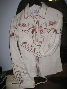 A women's western-style shirt.  Pearl buttons and embroidery galore!