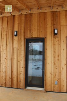 Exterior view of front door and covered porch showing reverse board and battan siding and Marvin Integrity door. Modern mountain farmhouse, cabin, corten steel metal roofing, cedar siding, pine paneling interior, marvin windows and doors, casement windows, glulam beams, tongue and groove floor decking, tongue and groove roof deck, SIPs panels, stained concrete floor, open floor plan, loft, alternating tread stair, architectural design, architect, mountain views, front porch, venacular design Cedar Siding, Exterior Siding, Stained Concrete, Concrete Floors, Casement Windows, Windows And Doors, Design Architect, Architecture Design, Steel Metal