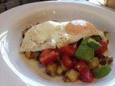 Potato & Apple Hash with fresh tomatoes & avacado, topped with a fried egg.