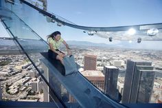 Sandra Brown, 40, rides the Skyslide on the 69th and 70th floors of the U.S. Bank Tower which is attached to the OUE Skyspace LA observation deck in downtown Los Angeles, California, U.S. June 20, 2016. REUTERS/Lucy Nicholson