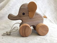 Pull along toy Elephant, a joyfully looking wooden animal on wheels with a string, will accompany your child in a lovely walk in a park or even at