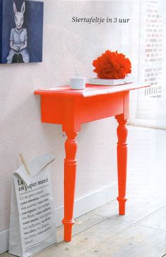 Brilliant! Table cut in half and painted a fabulous orange. use mounting brackets to stabilize . Great use of limited space, too...  put the other half in the next room so it seems like it's coming through the wall :)